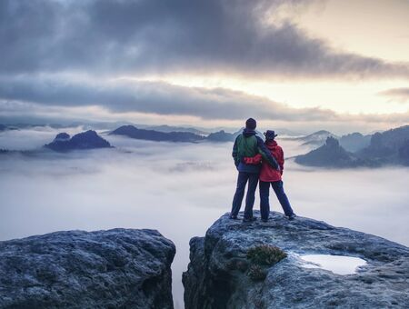 Lovely Couple looking at far sunrise in heavy clouds. The dark night in foggy mountains ends.