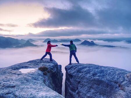 Hikers or climbers in mountains. Couple hold the light  high above danger gulch between rocks. Night photo in misty mountains. Lovers standing on rocky mountain peak