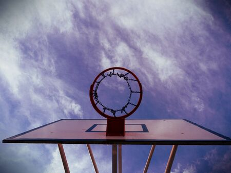Basketball rim, basketball net on a basketball court at a basketball game. the background is clear blue sky. Abstract filter.