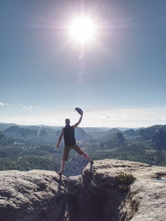 Hiker yelling with happiness on a mountain top. Man on mountain top hiking or climbing. Looking and enjoying inspirational sunshine landscape on rock 版權商用圖片