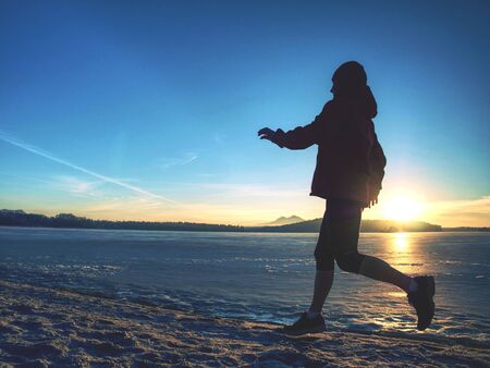 Fitness people, sport and healthy lifestyle concept - young woman in sport suit running along ice covered winter river.