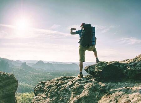 Reisender Mann mit Blick auf die Berge und Landschaftsfoto mit Smartphone, glänzendem Bildschirm Standard-Bild