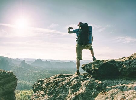 Traveler man looking at mountain view and making landscape photo using smartphone, shinning screen Stock Photo