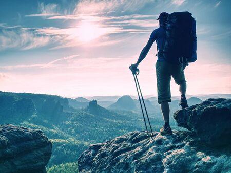 Genießen Sie die atemberaubende Aussicht von der Spitze der Welt. Wanderer ruhen sich aus, um die Landschaft darunter zu beobachten. Beliebtes Nordic Walking Standard-Bild
