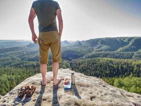 Hiker in shorts and blue singlet eat toasts for breakfast in rocks. Amazing summer morning in pure nature. Stock Photo