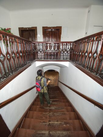 Hobby photographer takes photo of interior house built in 19th sentury. Wooden staircase in middle of burgher house.