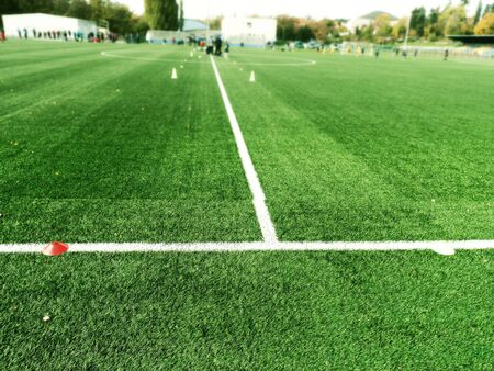 Cones are soccer training equipment on green artificial turf with blurry coach is training kid players background