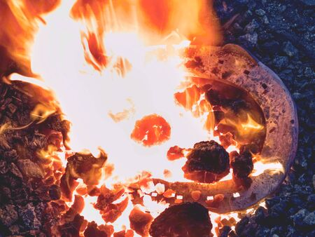 Detail of blacksmith  forge with strong flames. Long pliers hold the hot horse shoe. Фото со стока