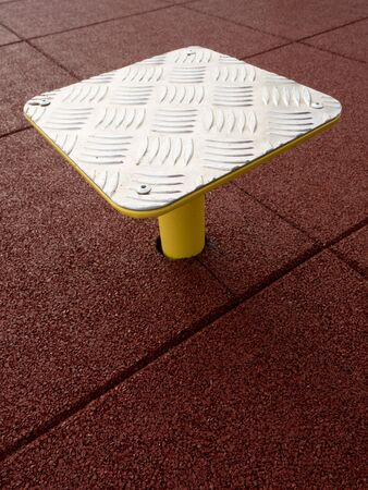 Outdoor exercising on step platform on red rubbery flexible background.  Safety tile floor made by plastic molding.