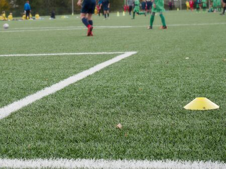 Close-up of soccer turf within kids training. Green grass with side boundary textured background