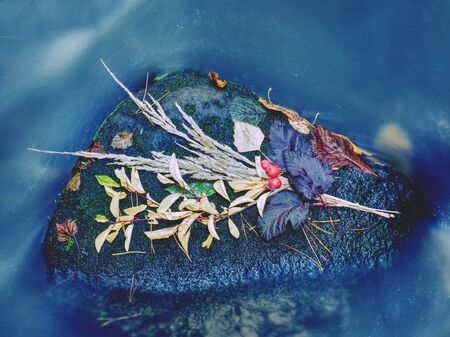 Hand made autumnal bouquet lay on stone in stream. Prepared still with bundles of colorful grass stalks and fall leaves
