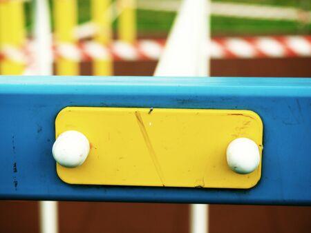 Frame for metal swedish ladder with yellow beams on ablurred dark background. Modern sports equipment, ffitness, gymnastics, bodybuilding training indoors.
