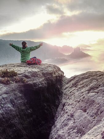 Hippie woman welcomes daybreak over misty valley on top of a mountain and enjoying the day. Rear view