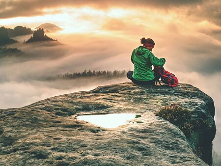 Back silhouette of hiker woman admiring amazing landscape over misty mountains in sunset time. Фото со стока