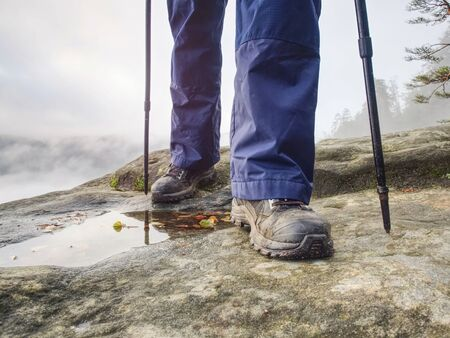 Woman legs in high waterproof boots make step over water pool on the rocky journey. Misty rainy weather in mountains