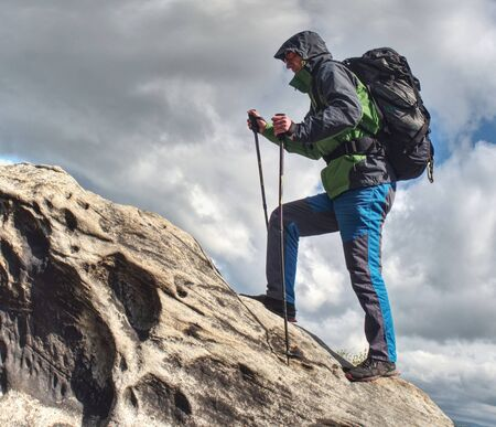 Climbing high up. Mountaineer with backpack hiking in mountains, climbing lifestyle. Man on top Zdjęcie Seryjne