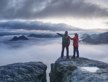 Lovers mirroring in water eye at mountain summit above thick mist.  Climbing couple at top of summit with amazing aerial view