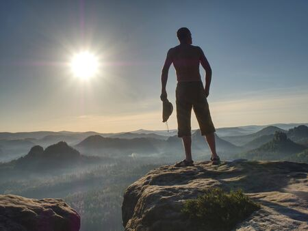 Shirtless man in checkered shorts and leather black cowboy hat decorated by beads looking at formations of rocks at horizon.