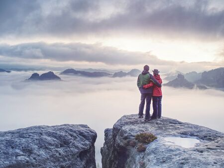 Happy couple with enjoy view after climbing top of rocky mountain.  Partners watch the beauty wild nature wood on the mountain