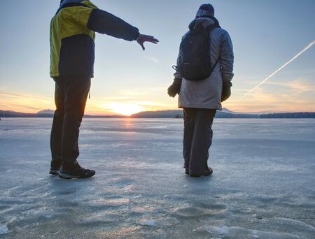 Cute couple in bay of frozen sea. They hold together at the frozen pond near sandy beach