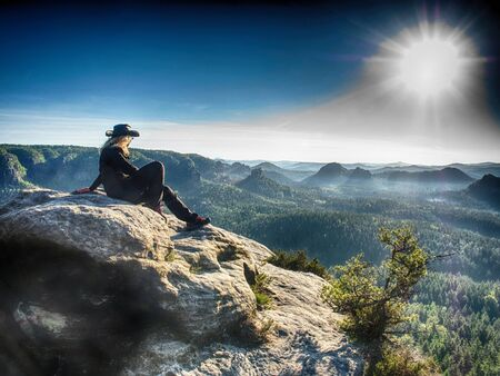 Rocky mountains with blond girl in a cowboy style. Sharp viewpoint above large valley