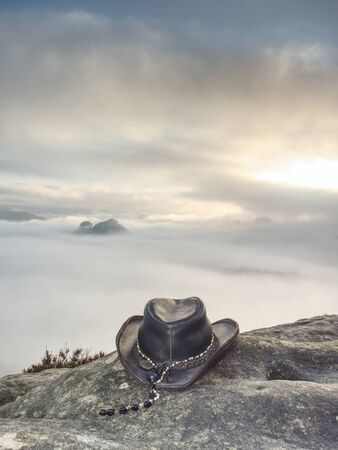 Cowboy hat ready on the rock. Leather cowboy accessories Reklamní fotografie