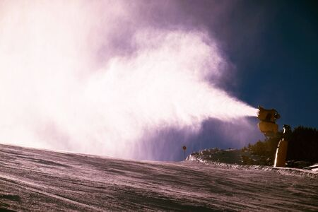 Snow cannons working hard on ski slope in Alps at sunny day.