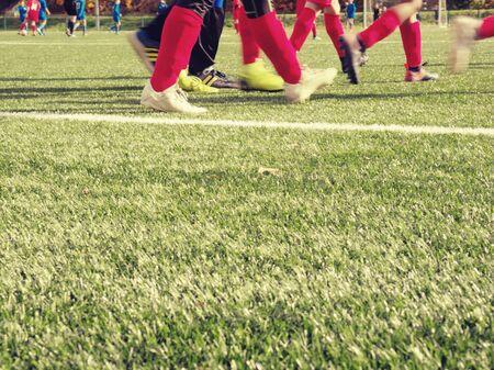Football turf detail while Soccer Team Training on Soccer Stadium. Dribbling soccer ball. Stock Photo