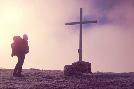 Hiker with backpack reaches the summit of mountain with cross. Snowy freeze mountain peak with meeting place. Success freedom and happiness achievement in mountains 스톡 콘텐츠
