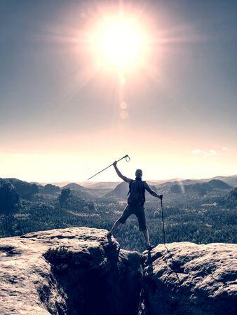 Erfolgreicher Mann, der vor Glück auf einem Berggipfel schreit. Erreichen des persönlichen Ziels