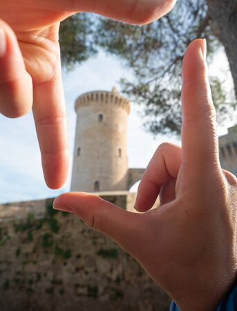 Female finger frame around Castell de Bellver tower, traveling concept.
