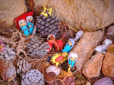 Childrens toy Nativity built in rocks. Presents from hikers walk around. Pintal Vermell pass, Mallorca island. Figures from a nativity scene or set with Jesus Christ, Mary and Joseph