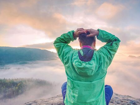 Young woman sit down on top of a mountain celebrate the day. Young lady hiker sitting in blue green windbreaker with red rucksack on sharp cliff Stock Photo