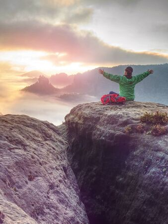 Girl on mountain summit hands raised over clouds. Travel Lifestyle success concept adventure active vacations outdoor