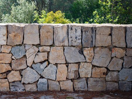 Stone wall of a fortress made from broken rocks.  A stone wall sunlit. Medieval, historical.