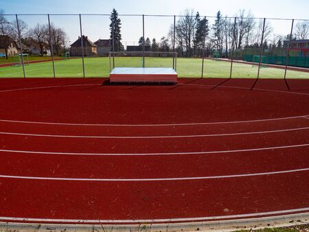 Curve of running tracks on outdoor stadium. Fotball gate and playground in the background Stock Photo