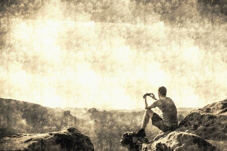 Hiker takes photos by smart phone on peak of mountain. Man in t-shirt and shorts takes photos with smartphone. Dreamy fogy landscape.  Calotype filter. Old photo style. Banco de Imagens