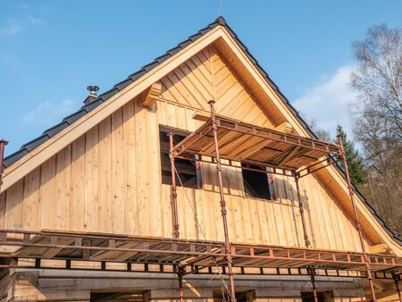 Wooden family house under construction, building house with foldable scaffolding