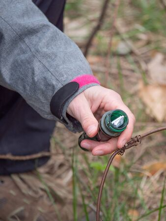 Geocaching container in hand. Woman removes list from locating ampoule for geocatching game.