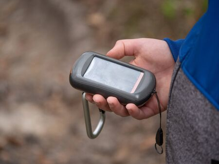 Hiker searching cache using global positioning device. Boy looking on the gps navigator in forest
