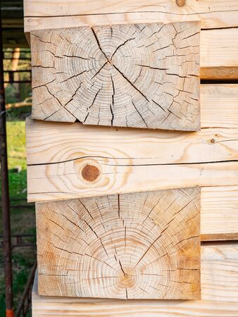 Smooth spruce logs joined together in the corner of wooden logs house. Rough cut unfinished wood set side by side. Stock Photo