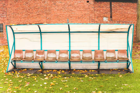 Old worn bench for reserve football players, old and ruined. Autumn morning with fallen leaves