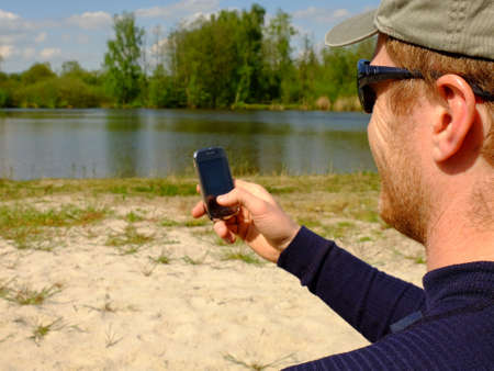 Man is sitting on the beach at lake and writing a sms on phone