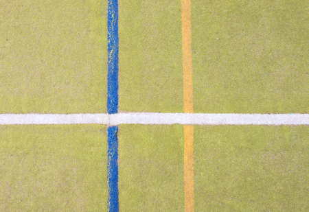 Worn out plastic hairy carpet on outside hanball court. Floor of sports playground with colorful marking lines. Stock Photo