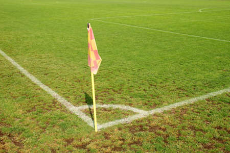 Yellow flag in corner of football field, lazy wind blowing