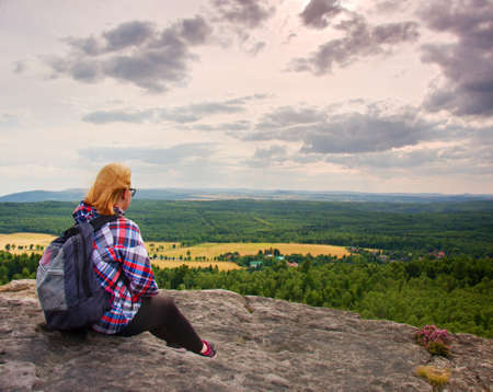 Young Woman hiker takes a rest on peak of the Mountain