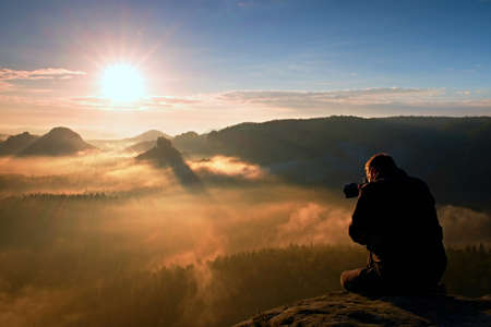 Tourist sit on the peak of sandstone rock and watching into colorful mist and fog in morning valley.