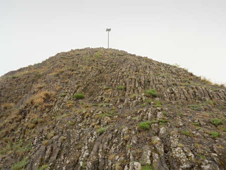 Sharp peak of basalt formation. Long basalt poles of cold volcano. Stockfoto