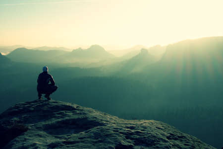 Hiker sits on a rocky peak and enjoy the scenery