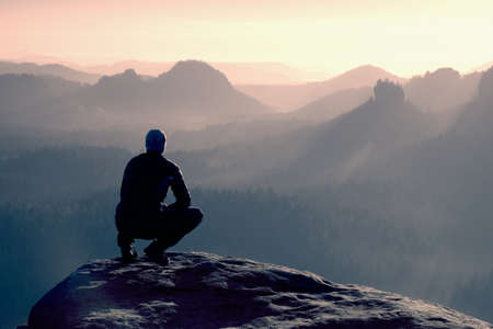 Young man in black sportswear is sitting on cliff's edge and looking to misty valley bellow Stockfoto